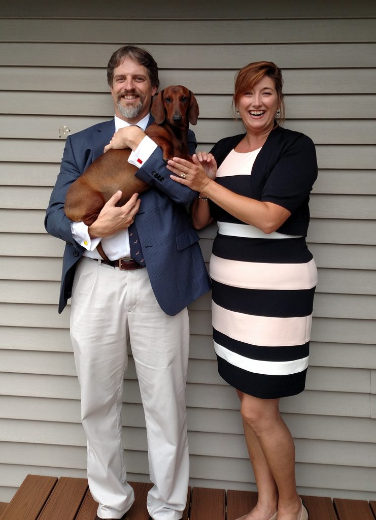 husband and wife holding brown, short-haired dachshund