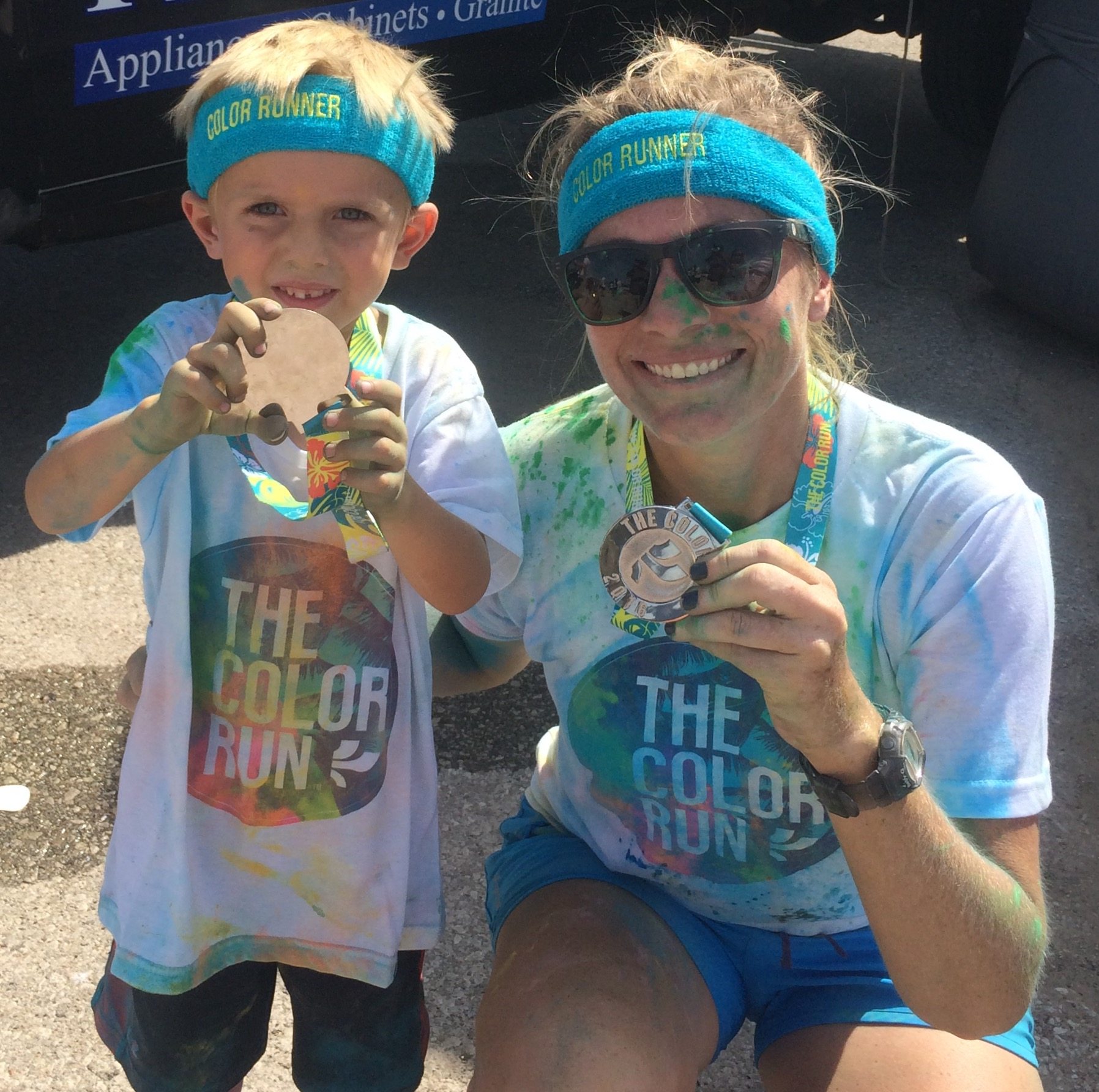 woman and young boy with medals after Color Run race